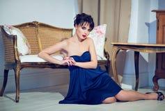 Όμορφο κορίτσι brunette σε μια μπλε συνεδρίαση φορεμάτων εκτός από τον καναπέ Στοκ φωτογραφία με δικαίωμα ελεύθερης χρήσης