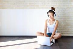 Όμορφο κορίτσι brunette στα ακουστικά που ακούει τη μουσική στο διάστημα αντιγράφων lap-top στοκ εικόνες