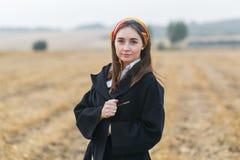 Όμορφο κορίτσι brunette στον τομέα, που φορά το μαύρο παλτό στοκ φωτογραφία