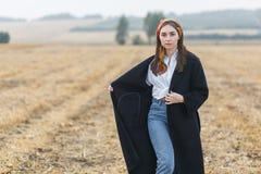 Όμορφο κορίτσι brunette στον τομέα, που φορά το μαύρο παλτό στοκ εικόνες