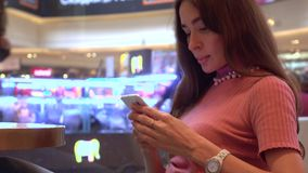 Όμορφο κορίτσι brunette στο ροζ που χρησιμοποιεί το τηλέφωνό της σε έναν καφέ Κινητός τηλεφωνικός εθισμός 4K βίντεο απόθεμα βίντεο