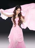 Όμορφο κορίτσι brunette στο ρόδινο φόρεμα με το φυσώντας ύφασμα ιστού Στοκ φωτογραφία με δικαίωμα ελεύθερης χρήσης