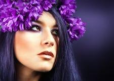 Όμορφο κορίτσι Brunette. Υγιής μακρυμάλλης. πορφυρά λουλούδια. Στοκ Φωτογραφία