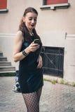 Όμορφο κορίτσι goth που χρησιμοποιεί το τηλέφωνο σε ένα πάρκο πόλεων Στοκ Φωτογραφίες