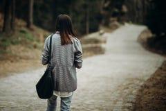 Όμορφο κορίτσι hipster με το μαύρο πορτοφόλι δέρματος που περπατά κάτω από pav Στοκ Φωτογραφίες