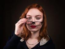 Όμορφο κορίτσι nerd ή νέα γυναίκα που κοιτάζει πέρα από eyeglasses Στοκ φωτογραφία με δικαίωμα ελεύθερης χρήσης