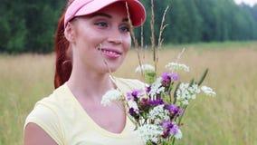 Όμορφο κορίτσι sniffs ΚΑΠ στα wildflowers στο θερινό βράδυ φιλμ μικρού μήκους