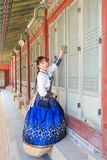 Όμορφο κορεατικό ντυμένο γυναίκα Hanbok που ανοίγει την πόρτα traditionl στο παλάτι στοκ εικόνες
