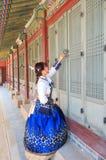 Όμορφο κορεατικό ντυμένο γυναίκα Hanbok που ανοίγει την πόρτα traditionl στο παλάτι στοκ φωτογραφίες