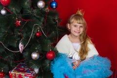 Όμορφο κοριτσάκι σε ένα φόρεμα και στη Παραμονή Πρωτοχρονιάς που χαμογελά και που ψάχνει ένα δώρο Στοκ Φωτογραφίες