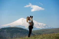 Όμορφο κοριτσιών βουνό beiside παραμονής κόλλεϊ συνόρων σκυλιών αγκαλιάσματος γραπτό στον τομέα στοκ φωτογραφίες