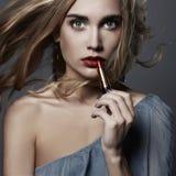 όμορφο κραγιόν κοριτσιών νέα γυναίκα που βάζει το κόκκινο κραγιόν Στοκ Φωτογραφίες