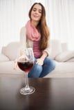 Όμορφο κρασί κατανάλωσης brunette στον καναπέ Στοκ Εικόνα