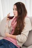 Όμορφο κρασί κατανάλωσης brunette στον καναπέ Στοκ Φωτογραφία