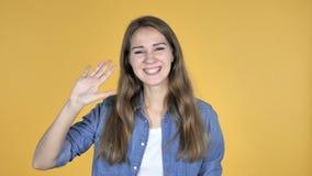 Όμορφο κυματίζοντας χέρι γυναικών για να καλωσορίσει απομονωμένος στο κίτρινο υπόβαθρο απόθεμα βίντεο