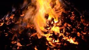 Όμορφο κόκκινο - καυτός καμμένος σωρός χοβόλεων με τις ζωηρόχρωμες φλόγες στη χειμερινή νύχτα