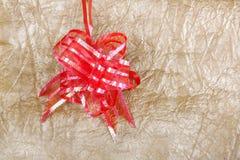 Όμορφο κόκκινο τόξο για τη διακόσμηση δώρων στον αφηρημένο χρυσό backgroun Στοκ φωτογραφία με δικαίωμα ελεύθερης χρήσης
