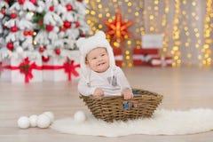 Όμορφο λίγο αγοράκι γιορτάζει τα Χριστούγεννα Νέες διακοπές έτους ` s Μωρό στα περιστασιακά ενδύματα Χριστουγέννων κοστουμιών με  Στοκ Εικόνα