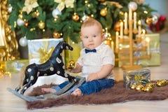 Όμορφο λίγο αγοράκι γιορτάζει τα Χριστούγεννα Νέες διακοπές έτους ` s Μωρό στα περιστασιακά ενδύματα Χριστουγέννων κοστουμιών με  Στοκ Εικόνες