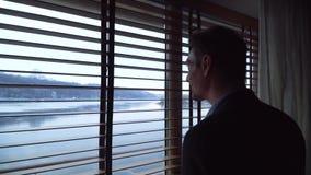 Όμορφο λεπτό άτομο που φαίνεται έξω το παράθυρο μέσω των τυφλών Η άποψη από το παράθυρο του ποταμού και του λόφου απόθεμα βίντεο