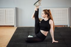 Όμορφο λεπτό brunette που κάνει μερικές τεντώνοντας ασκήσεις σε μια γυμναστική Στοκ Φωτογραφίες
