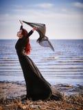 Όμορφο λυπημένο κορίτσι goth με το ύφασμα στα χέρια που στέκονται στην ακροθαλασσιά Στοκ Φωτογραφίες