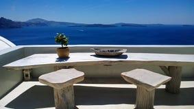 Όμορφο μέρος Oia με έναν πίνακα και καρέκλες για τις ρομαντικές συνεδριάσεις - μεγάλη άποψη της φωτεινής μπλε θάλασσας στοκ εικόνα
