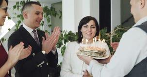Όμορφο μέσο ηλικίας φυσώντας κερί γυναικών στο κέικ φιλμ μικρού μήκους