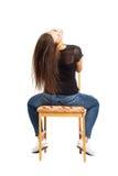 Όμορφο μακρυμάλλες brunette που εγκαθιστά προς τα πίσω στην καρέκλα Στοκ Εικόνα