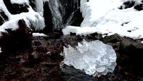 Όμορφο μεγάλο κομμάτι του πάγου με τις αφηρημένες ρωγμές Πεσμένος καταρράκτης φυσητήρων παγακιών, πετρώδης τράπεζα ρευμάτων φιλμ μικρού μήκους