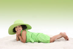 όμορφο μεγάλο πράσινο καπέλο κοριτσιών που βάζει την άμμο που φορά τις νεολαίες Στοκ Εικόνες