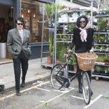 Όμορφο μεμβρανοειδές ψηλό πρότυπο κοριτσιών σε ένα μαντίλι με το ποδήλατο στην αγορά οδικών λουλουδιών της Κολούμπια Στοκ Φωτογραφίες