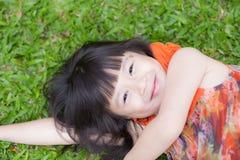 Όμορφο μικρό κορίτσι Ασιάτης πορτρέτου ενός χαμόγελου που βρίσκεται στην πράσινη χλόη στο πάρκο στοκ φωτογραφίες