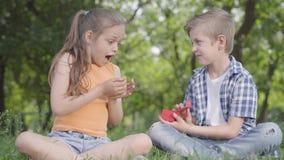 Όμορφο μικρό κορίτσι και η όμορφη συνεδρίαση αγοριών στη χλόη από κοινού Το αγόρι που παίρνει ένα μικρό κόκκινο κιβώτιο και που α φιλμ μικρού μήκους