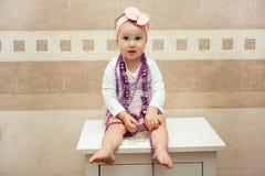 Όμορφο μικρό κορίτσι με ένα ρόδινο τόξο και πορφυρές χάντρες Στοκ εικόνες με δικαίωμα ελεύθερης χρήσης