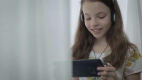 Όμορφο μικρό κορίτσι με τα ακουστικά που προσέχει τα αστεία βίντεο στην ταμπλέτα και τα γέλια απόθεμα βίντεο