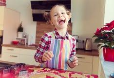Όμορφο μικρό κορίτσι με τις αστείες πλεξίδες που κατασκευάζει τα μπισκότα Χριστουγέννων Στοκ Φωτογραφίες