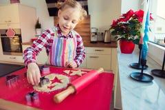 Όμορφο μικρό κορίτσι με τις αστείες πλεξίδες που κατασκευάζει τα μπισκότα Χριστουγέννων Στοκ φωτογραφία με δικαίωμα ελεύθερης χρήσης