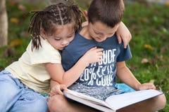 Όμορφο μικρό κορίτσι με τις πλεξίδες και ένα αγόρι που διαβάζει ένα Si βιβλίων Στοκ Φωτογραφίες
