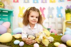 Όμορφο μικρό κορίτσι με τους νεοσσούς και chikens στο χορτοτάπητα Στοκ Φωτογραφίες