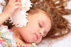 Όμορφο μικρό κορίτσι με το θαλασσινό κοχύλι στοκ εικόνες