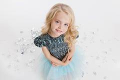 Όμορφο μικρό κορίτσι με το σγουρό ξανθό hairstyle που εγκαθιστά στο κόμμα διακοπών στο φόρεμα με τα τσέκια Ασημένιο φύλλο αλουμιν Στοκ Εικόνες
