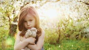 Όμορφο μικρό κορίτσι που αγκαλιάζει ένα σκυλί παιχνιδιών απόθεμα βίντεο