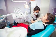 Όμορφο μικρό κορίτσι που ανοίγει το στόμα του ευρέως κατά τη διάρκεια της μεταχείρησης των δοντιών της από τον οδοντίατρο Στοκ Εικόνες
