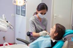 Όμορφο μικρό κορίτσι που ανοίγει το στόμα του ευρέως κατά τη διάρκεια της μεταχείρησης των δοντιών της από τον οδοντίατρο Στοκ φωτογραφίες με δικαίωμα ελεύθερης χρήσης