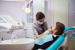 Όμορφο μικρό κορίτσι που ανοίγει το στόμα του ευρέως κατά τη διάρκεια της μεταχείρησης των δοντιών της από τον οδοντίατρο Στοκ Φωτογραφίες