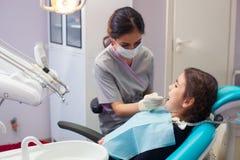 Όμορφο μικρό κορίτσι που ανοίγει το στόμα του ευρέως κατά τη διάρκεια της μεταχείρησης των δοντιών της από τον οδοντίατρο Στοκ Εικόνα