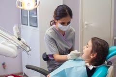 Όμορφο μικρό κορίτσι που ανοίγει το στόμα του ευρέως κατά τη διάρκεια της μεταχείρησης των δοντιών της από τον οδοντίατρο Στοκ Φωτογραφία