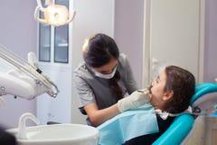 Όμορφο μικρό κορίτσι που ανοίγει το στόμα του ευρέως κατά τη διάρκεια της μεταχείρησης των δοντιών της από τον οδοντίατρο Στοκ εικόνα με δικαίωμα ελεύθερης χρήσης