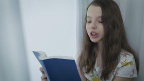Όμορφο μικρό κορίτσι που διαβάζει ένα ενδιαφέρον βιβλίο από το παράθυρο απόθεμα βίντεο